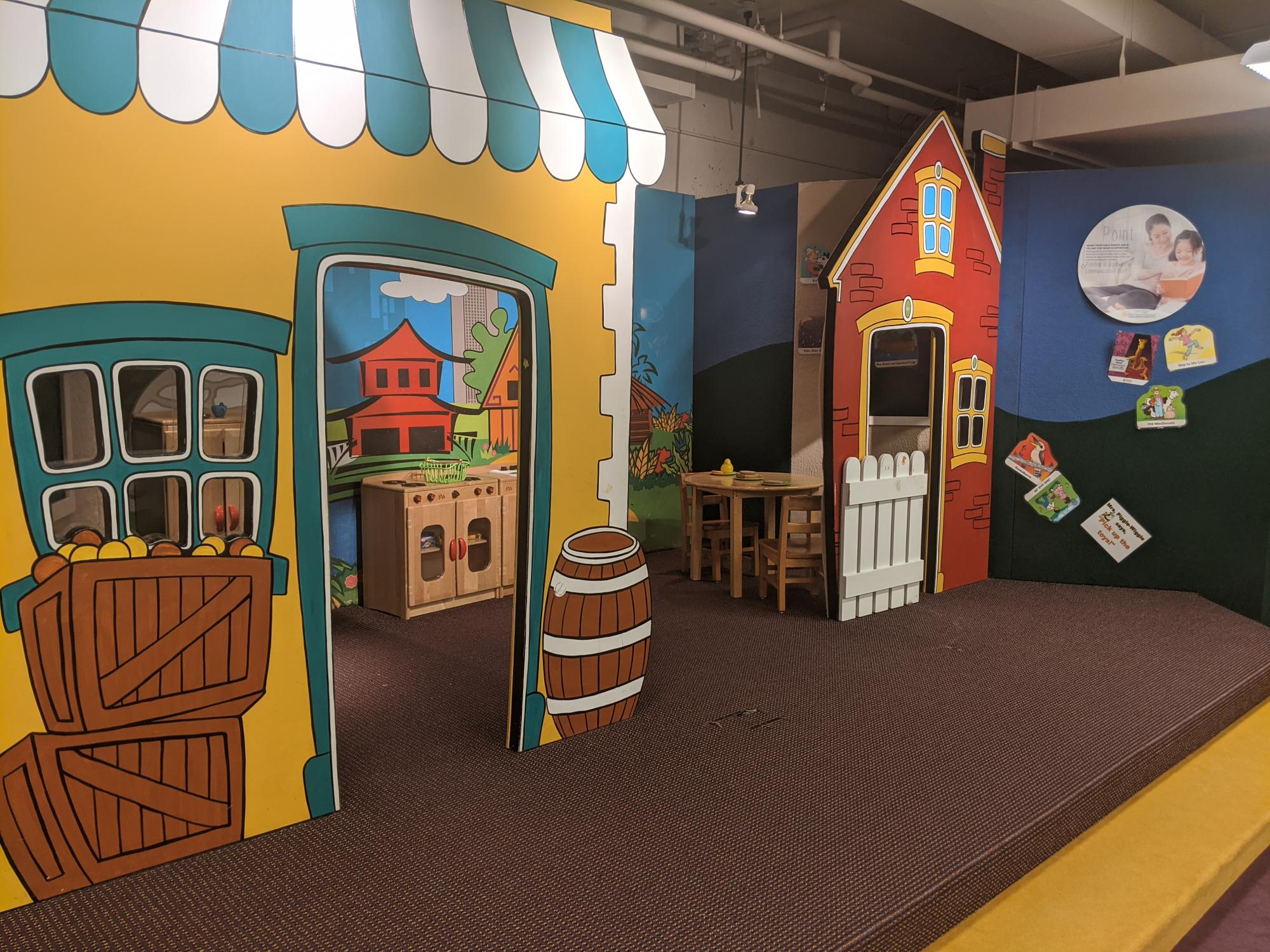 Child-sized pretend store-fronts and house buildings create a colorful space for pretend play.
