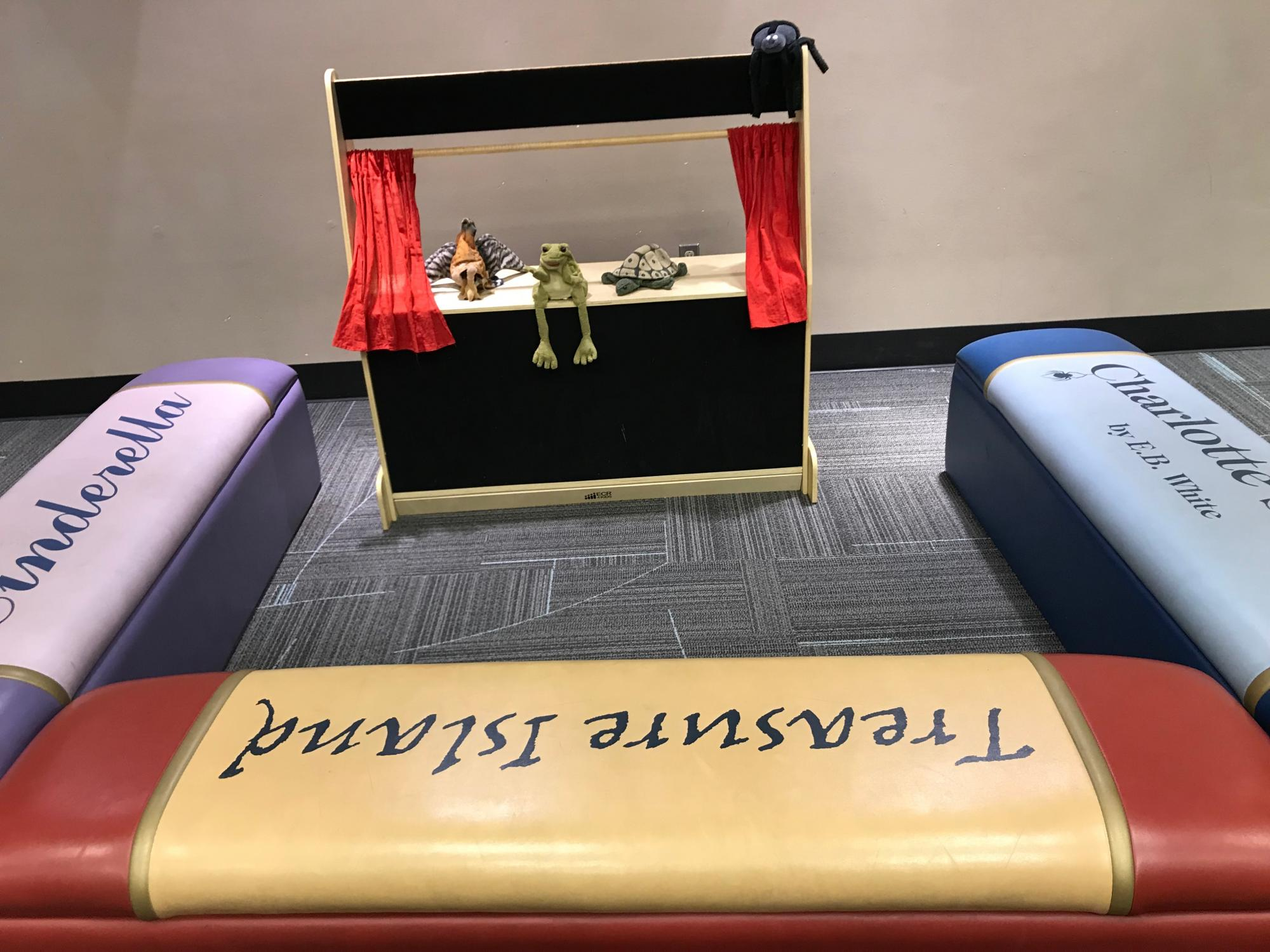 Image shows a trio of book benches in front of a puppet stage.
