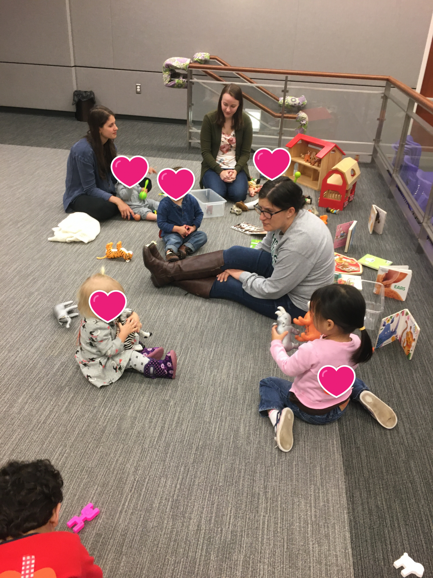 Caregivers and their children play with toys and read board books.