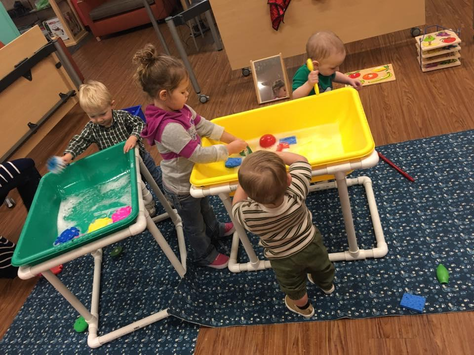 Children playing in water sensory bins.