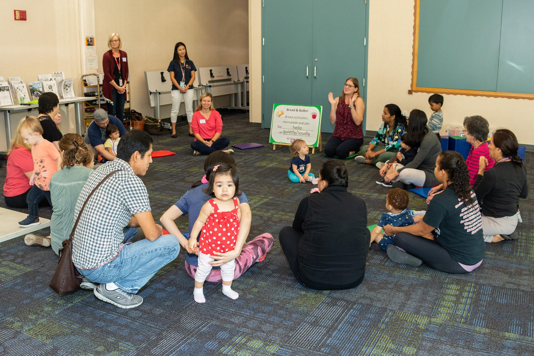 Families participate in circle time at a playgroup session.