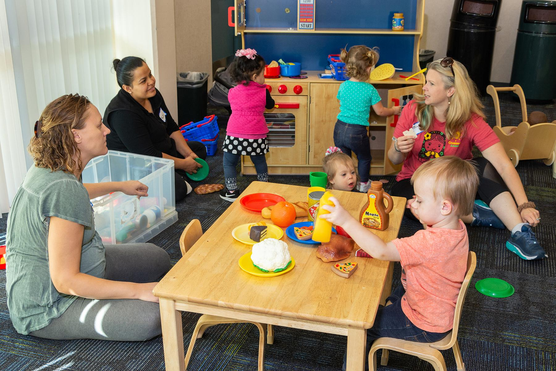 Parents and children play together in a play kitchen at a playgroup session.