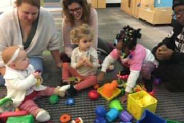 Three mom and baby pairs playing with toys during Babygarten