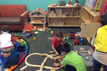 Children building train tracks.