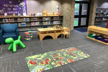 Image shows a library play area with city rug, green sit-on toy, books, dinosaurs, and blocks.