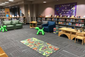 Image shows a library play area with city rug, green sit-on toys, and upholstered chairs