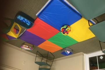 infant play area with toys and colorful mat
