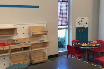 A glimpse of our play kitchen, which includes a small table and four red chairs and wooden kitchen components on the wall.