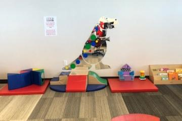 Joplin Public Library Children Department infant and toddler play area includes colorful padded flooring, blocks, and a large dinosaur mirror