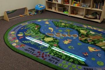 Rug with a lake on the floor. There is a toy chest in the back. Baby mirror on the floor.