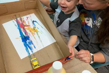 Toddler paints tracks with cars at process art station.