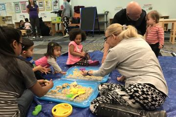 Families playing with kinetic sand at sensory station.