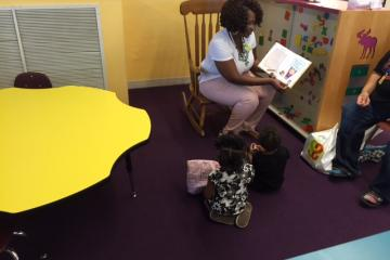 Children's Librarian reading to young children during event.