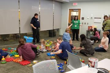 Caregivers and children sit on the floor playing with a variety of toys.