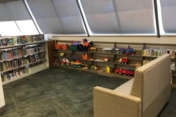 Open play area with a variety of toys on shelves. There is a comfortable couch nearby.