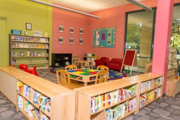 Early childhood space featuring books, LEGO table, toys, and parenting collection.