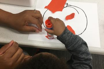 A black child practices ripping orange paper and gluing it on a pumpkin picture with the help of a black caregiver.