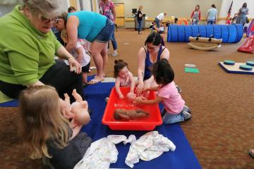 Washing baby dolls at Baby Club
